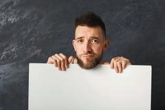 Homme triste bel tenant le livre blanc dans le studio Photographie stock