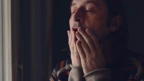 Homme triste caucasien adulte se tenant prêt la fenêtre de son salon et pleurant de désespoir banque de vidéos