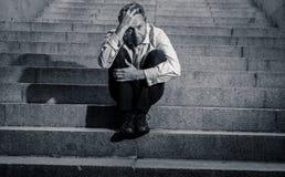 Homme triste déprimé d'affaires dans le désespoir total abattant la séance désespérée et frustrante dans des escaliers de ville photos libres de droits