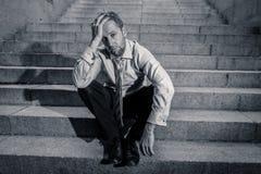 Homme triste déprimé d'affaires dans le désespoir total abattant la séance désespérée et frustrante dans des escaliers de ville photos stock