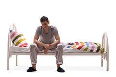 Homme triste dans des pyjamas se reposant sur un lit Image libre de droits