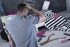 Homme triste dans la chambre malpropre photographie stock libre de droits