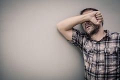 Homme triste du portrait un se tenant près d'un mur et des couvertures son visage Images libres de droits
