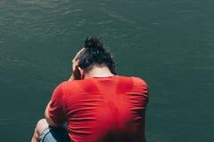 Homme triste et déprimé dans la baie se reposante de chemise rouge l'eau verte sombre Photos stock