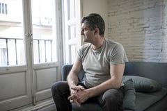 Homme triste et inquiété avec les cheveux gris reposant à la maison le regard de divan Images libres de droits