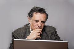 Homme triste et inquiété d'affaires avec un ordinateur portatif Photo libre de droits