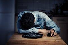Homme triste et seul buvant après dîner photos stock