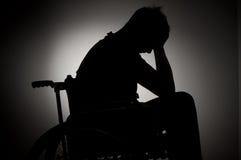 Homme triste s'asseyant sur le fauteuil roulant images stock