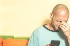 Homme triste tenant son téléphone portable dans des ses mains et cri parce que son amie se cassent avec lui au-dessus du message  photos stock