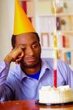 Homme triste utilisant la chemise bleue et le chapeau se reposant par la table avec le gâteau dans le burning avant et simple de  Photos libres de droits