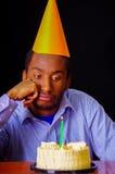 Homme triste utilisant la chemise bleue et le chapeau se reposant par la table avec le gâteau dans le burning avant et simple de  Image stock
