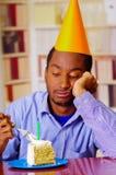 Homme triste utilisant la chemise bleue et le chapeau se reposant par la table avec le morceau de gâteau dans l'avant, regardant  Image libre de droits
