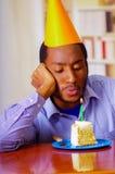 Homme triste utilisant la chemise bleue et le chapeau se reposant par la table avec le morceau de gâteau dans l'avant, regardant  Photo stock