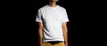 Homme, type dans le support blanc vide de T-shirt sur un fond noir, moquerie, l'espace libre, logo, conception, calibre pour la c Photographie stock libre de droits