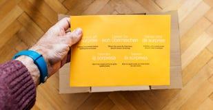 Homme unboxing Amazone carton de COM contenant une enveloppe de surprise Photographie stock