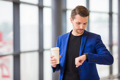 Homme urbain avec du café à l'intérieur dans l'aéroport Un jeune homme est en retard pour un vol et regarde sa montre Photo stock