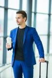 Homme urbain avec du café à l'intérieur dans l'aéroport Veste de port de costume de jeune garçon occasionnel Homme caucasien avec Photos stock