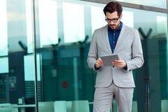 Homme urbain d'affaires avec l'ordinateur portable dehors dans l'aéroport Image libre de droits