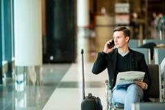 Homme urbain d'affaires parlant au téléphone intelligent à l'intérieur dans l'aéroport Veste de port de costume de jeune homme d' Photographie stock libre de droits