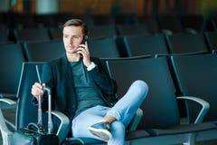 Homme urbain d'affaires parlant au téléphone intelligent voyageant à l'intérieur dans l'aéroport Veste de port de costume de jeun Images stock