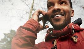 Homme urbain de sourire heureux de hippie de vue de plan rapproché jeune portant les vêtements informels et à l'aide du téléphone Image libre de droits