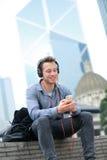 Homme urbain sur les écouteurs de port de téléphone intelligent Image libre de droits