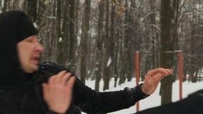 Homme utile dans un costume noir de sports avec un capot, exécutant étirant des muscles de jambe sur un vieux, barre horizontale  clips vidéos