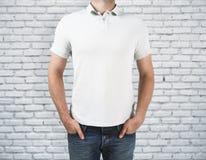 Homme utilisant la chemise vide sur le fond de brique Image stock