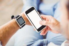 Homme utilisant la montre intelligente et à l'aide du smartphone photographie stock