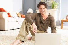 Homme utilisant la pose de détente d'ordinateur portatif sur la couverture à la maison Photos libres de droits