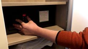 Homme utilisant le coffre-fort de chambre d'hôtel banque de vidéos