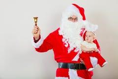 Homme utilisant le costume du père noël tenant le bébé Image stock