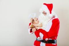 Homme utilisant le costume du père noël tenant le bébé Photographie stock