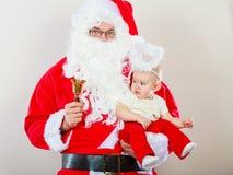 Homme utilisant le costume du père noël tenant le bébé Photographie stock libre de droits