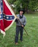 Homme utilisant le costume historique tenant le drapeau confédéré Images stock