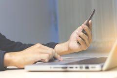 Homme utilisant le smaptphone et l'ordinateur portable photos stock