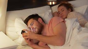 Homme utilisant le smartphone tandis que l'amie dort banque de vidéos