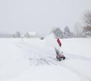 Homme utilisant le ventilateur de neige sur le lecteur neigeux Photo libre de droits