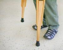 Homme utilisant les béquilles en bois sur le fond de plancher de sol de mosaïque photos libres de droits