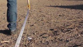 Homme utilisant mètres géodésiques de roulette les 100 sur le sable de plancher banque de vidéos