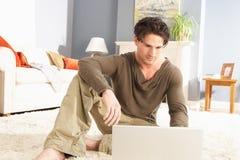 Homme utilisant se reposer de détente d'ordinateur portatif sur la couverture à la maison Photographie stock