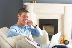 Homme utilisant se reposer de détente d'ordinateur portatif sur le sofa à la maison Image libre de droits