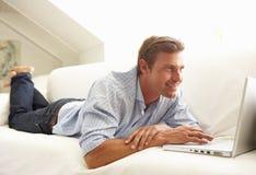 Homme utilisant se reposer de détente d'ordinateur portatif sur le sofa à la maison Photographie stock