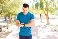 Homme vérifiant des comptes d'étapes sur la montre intelligente en parc images stock