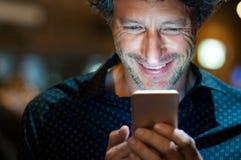 Homme vérifiant le smartphone la nuit photo stock