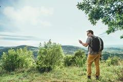 Homme vérifiant le téléphone intelligent sur la montagne Image libre de droits