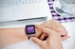 Homme vérifiant le temps sur la montre intelligente Ordinateur portable et café dans le backgroun Photos libres de droits