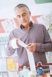 Homme vérifiant un reçu d'épicerie photo stock