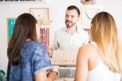 Homme vendant des bijoux à un magasin Image stock