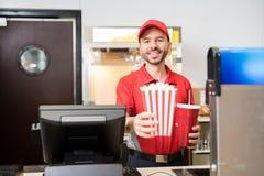 Homme vendant des casse-croûte à la salle de cinéma photos stock